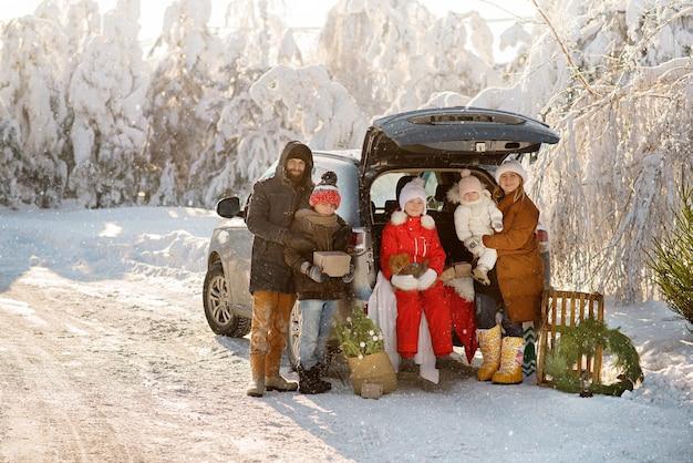 Piękna rodzina stoi obok bagażnika suv-a w zimowym lesie, świętuje boże narodzenie