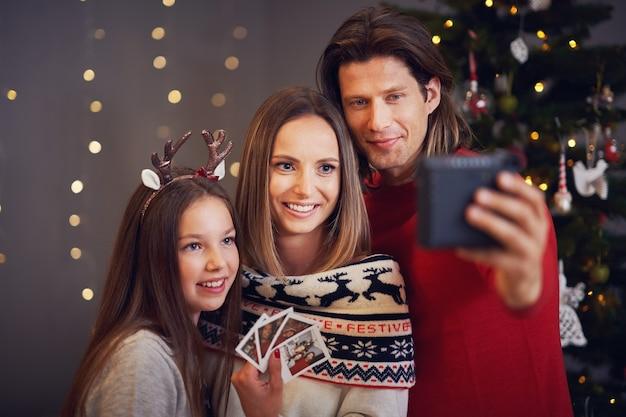 Piękna rodzina świętująca boże narodzenie w domu i robiąca natychmiastowe zdjęcia