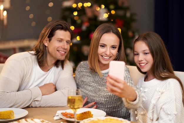 Piękna rodzina świętująca boże narodzenie w domu i robiąca selfie