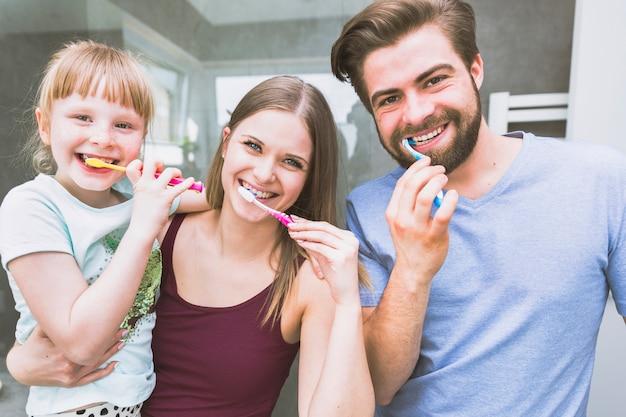 Piękna rodzina szczotkuje zęby dla kamery