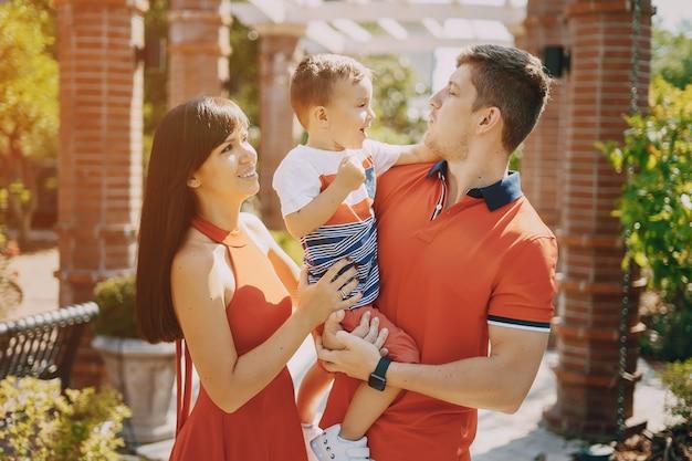 Piękna rodzina w czerwonej chodzącej po ulicy i parku