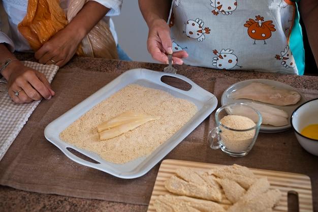 Piękna rodzina w domu, gotowanie i wspólna zabawa - babcia pokazuje, jak gotować ciasteczka i ryby - styl życia w domu - cieszą się kaukaską kobietą i dojrzałą kobietą