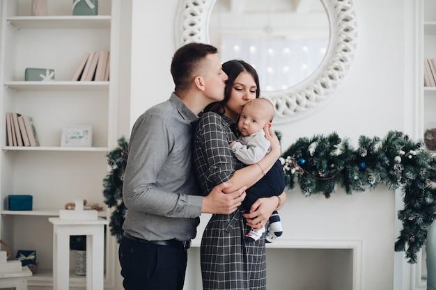Piękna rodzina z dzieckiem, ciesząc się razem świąteczną atmosferą