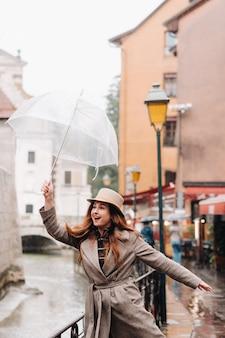 Piękna romantyczna dziewczyna w płaszczu i kapeluszu z przezroczystym parasolem w annecy. francja. dziewczyna w kapeluszu we francji.