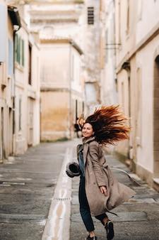 Piękna romantyczna dziewczyna w płaszczu z rozpuszczonymi włosami biegnie po starym mieście awinion. francja. dziewczyna w płaszczu we francji.
