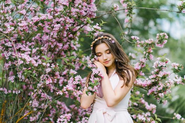 Piękna romantyczna dziewczyna w różowej delikatnej sukni stoi na wiosnę w pobliżu krzaka różowych kwiatów weigela i dotyka gałęzi