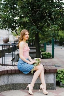 Piękna romantyczna dziewczyna w różowym topie i dżinsowej spódnicy z bukietem róż i siedząca na ławce na placu miejskim