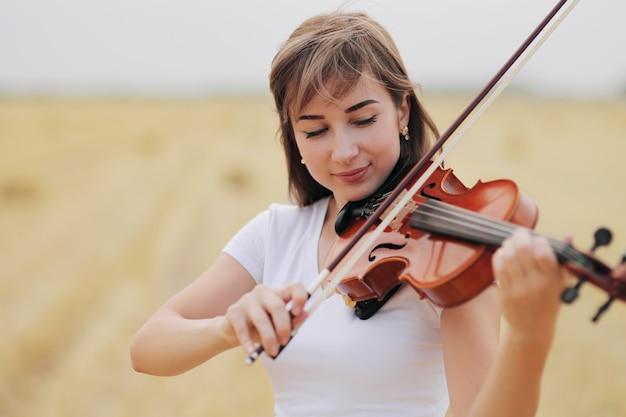 Piękna romantyczna dziewczyna z luźnymi włosami gra na skrzypcach w polu po zbiorach