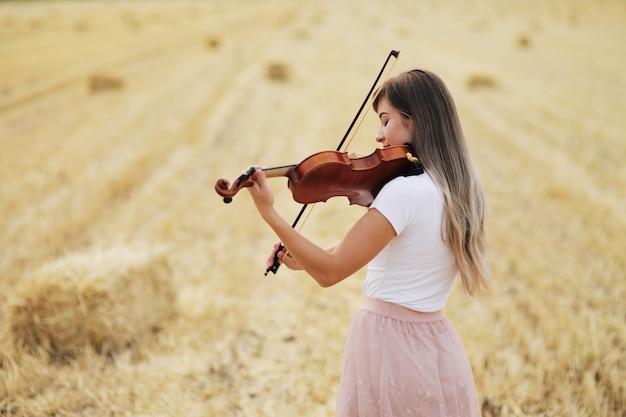 Piękna romantyczna dziewczyna z luźnymi włosami, grająca na skrzypcach w polu po zbiorach