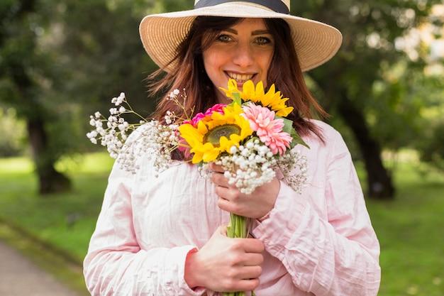 Piękna romantyczna kobieta w kapeluszowych mienie kwiatach