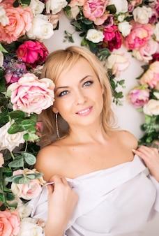 Piękna romantyczna młoda blondynki kobieta z naturalny makeup pozować kwiaty, kwiat ściana w menchiach. koncepcja perfum i kosmetyków