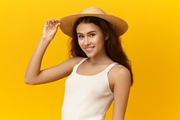 Piękna romantyczna młoda kobieta ubrana w słomkowy kapelusz i biały podkoszulek, ciesząc się wakacjami