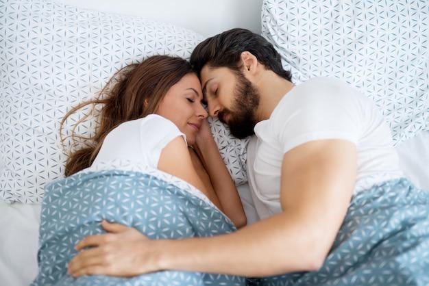 Piękna romantyczna para zakochanych śpiących razem przytulona na łóżku w domu lub hotelu.