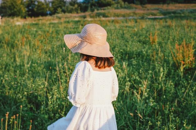 Piękna romantyczna preteen dziewczyna w białej sukni i słomkowym kapeluszu od tyłu na łące, złota godzina