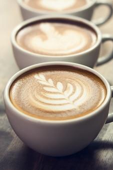 Piękna rosetta wzoru latte sztuki kawa w filiżankach