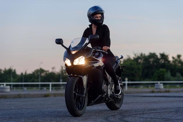 Piękna rowerzysta dziewczyna na jej super motocykl na zewnątrz miejskiego parkingu na tle pejzażu i zachodu słońca.