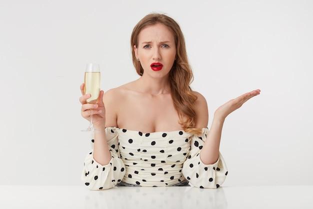 Piękna, rozczarowana młoda dama o długich blond włosach, z czerwonymi ustami w sukience w kropki, unosząca kieliszek szampana, chce zadać pytanie patrząc na aparat odizolowany na różowym tle.