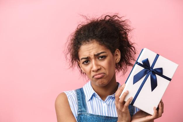 Piękna rozczarowana młoda kobieta afryki, trzymając pudełko na różowo