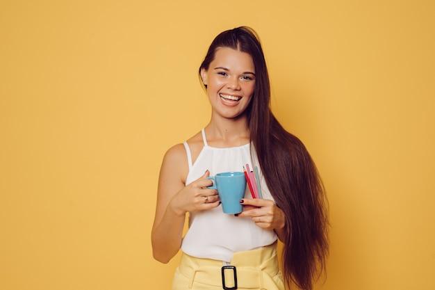 Piękna roześmiana brunetka z długimi włosami w białej bluzce i żółtych spodniach podczas przerwy z filiżanką kawy i kredkami na żółtym tle.