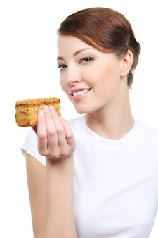 Piękna roześmiana kobieta z ciastem na białym tle