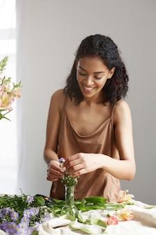 Piękna rozochocona afrykańska kobiety kwiaciarnia ono uśmiecha się robić bukietowi w kwiatu sklepie nad biel ścianą.