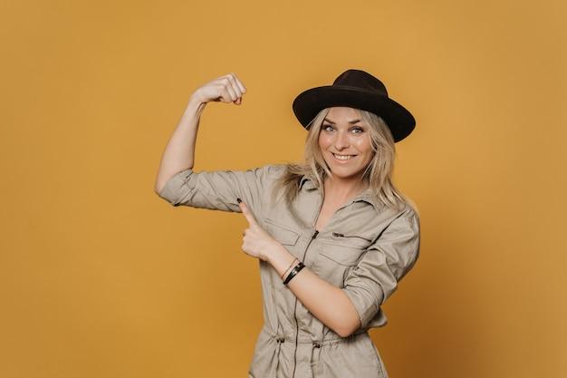 Piękna rozochocona blondynki kobieta w przypadkowych kombinezonach i kapeluszowym uśmiechu szeroko, demonstruje jej biceps i wskazując na niego drugą ręką, wygląda radośnie, na żółtym tle. koncepcja pozytywnych ludzi.