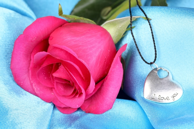 Piękna różowa róża z zawieszką w kształcie serca