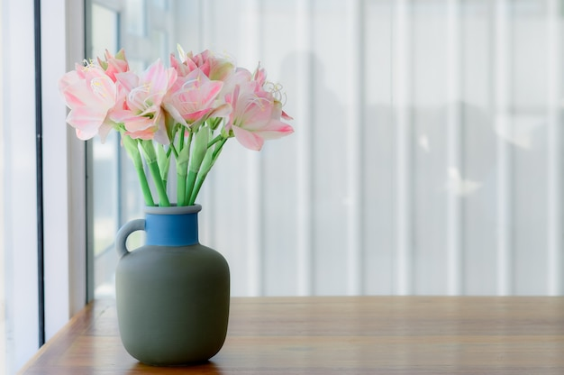 Piękna różowa sztuczna leluja w szarej ceramicznej wazie na brown drewna stołu tle.