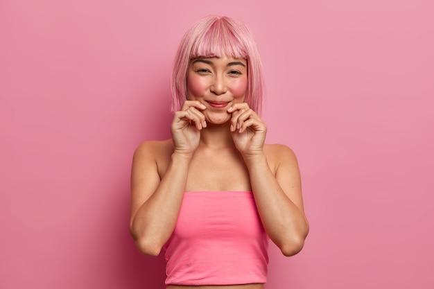 Piękna różowowłosa azjatka uśmiecha się przyjemnie, trzyma dłonie przy ustach, chętnie słuchając przyjemnych wiadomości, nosi różową bluzkę, która stoi w domu. monochromia. etniczna dziewczyna z modną fryzurą wyraża dobre emocje