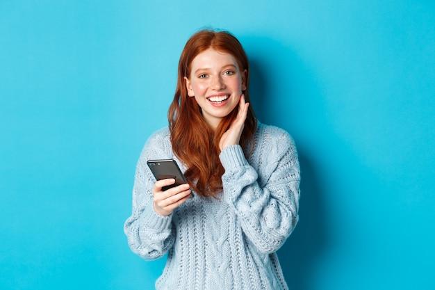 Piękna ruda dziewczyna w swetrze, uśmiechająca się do kamery, korzystająca z aplikacji na telefon komórkowy, stojąca ze smartfonem na niebieskim tle