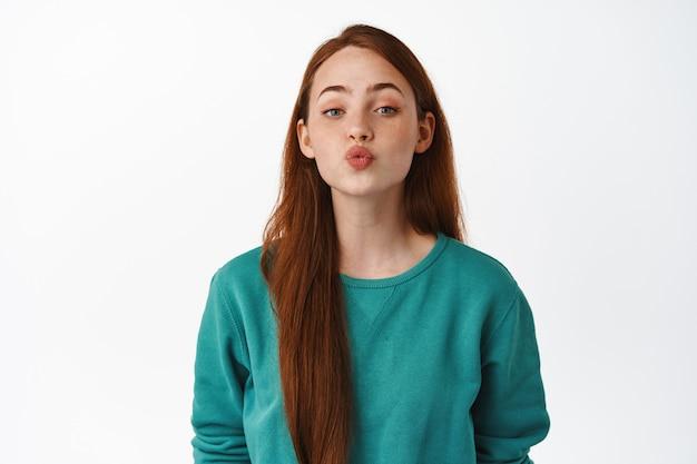 Piękna ruda kaukaska dziewczyna całuje, marszczy usta i pochyla się do pocałunku, romantycznego związku lub randki, stojąc zalotnie na białym.