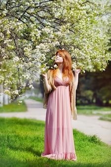 Piękna ruda kobieta marzy w pobliżu drzewa wiśni kwitnąć wiosną
