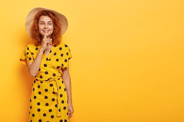 Piękna ruda kobieta pozuje w żółtej sukience polka i słomkowym kapeluszu
