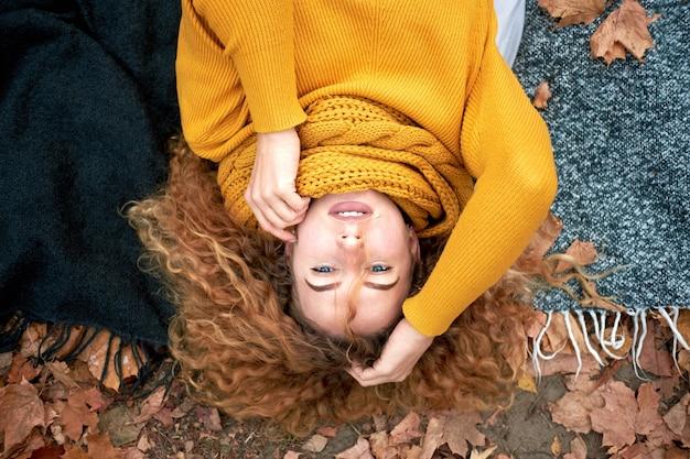 Piękna ruda kręcona wesoła śliczna kobieta ubrana w modny jesienny sweter i szalik leżący na jesiennych liściach