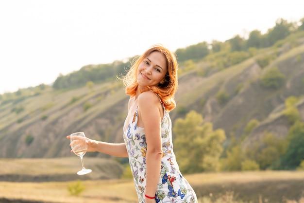 Piękna rudowłosa dziewczyna bawi się i tańczy na polu o zachodzie słońca