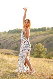 Piękna rudowłosa dziewczyna bawi się i tańczy na polu o zachodzie słońca.