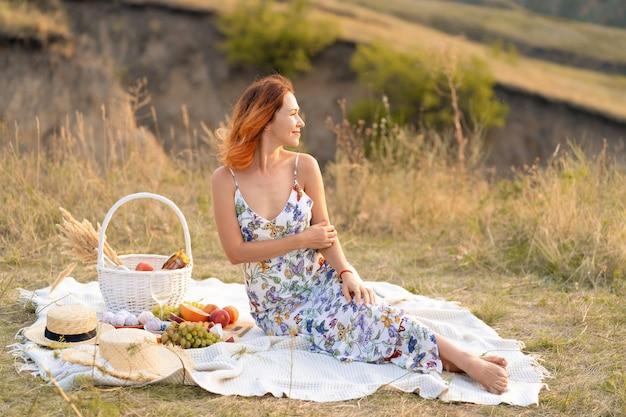 Piękna rudowłosa dziewczyna cieszy się zachodem słońca na naturze. piknik w terenie.