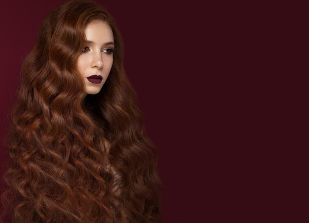 Piękna rudowłosa dziewczyna o idealnie kręconych włosach i klasycznym makijażu. piękna twarz.