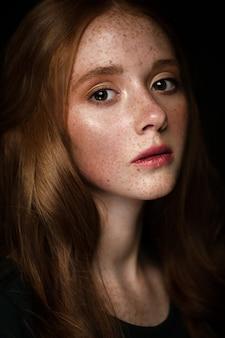 Piękna rudowłosa dziewczyna o idealnie kręconych włosach i klasycznym makijażu