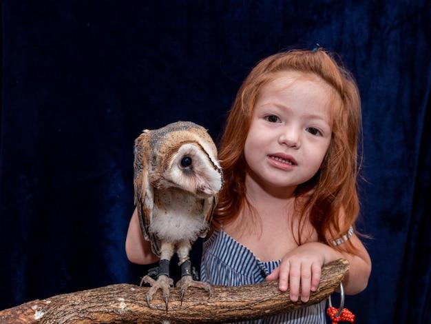 Piękna rudowłosa dziewczyna robi zdjęcie z jej sowa.