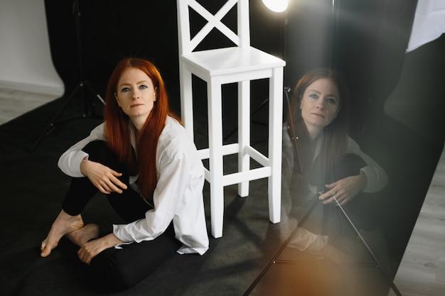 Piękna rudowłosa dziewczyna siedzi na podłodze w studio