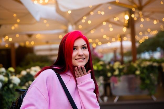 Piękna rudowłosa dziewczyna wieczorem na oświetlonej ulicy miasta.