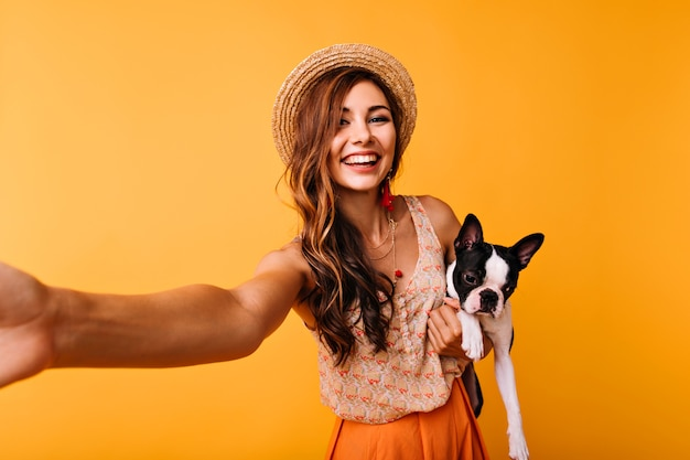 Piękna rudowłosa dziewczyna z buldogiem francuskim dokonywanie selfie. zainspirowana modelka pozuje na pomarańczowo z czarnym szczeniakiem.