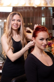 Piękna rudowłosa dziewczyna z długimi włosami fryzjerka w salonie piękności tka francuski warkocz. profesjonalna pielęgnacja włosów i tworzenie fryzur.