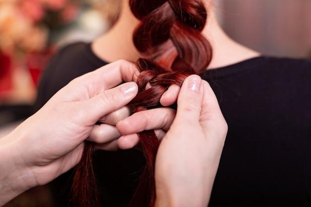 Piękna rudowłosa dziewczyna z długimi włosami fryzjerka wplata francuski warkocz