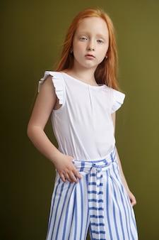 Piękna rudowłosa dziewczyna z długimi włosami i pięknymi dużymi niebieskimi oczami