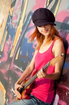 Piękna rudowłosa dziewczyna z gitarą i graffiti ścianą