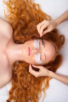 Piękna rudowłosa dziewczyna z kręconymi włosami. profesjonalny makijaż i pielęgnacja skóry.