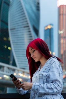 Piękna rudowłosa dziewczyna z smartphone wieczorem na oświetlonej ulicy miasta.