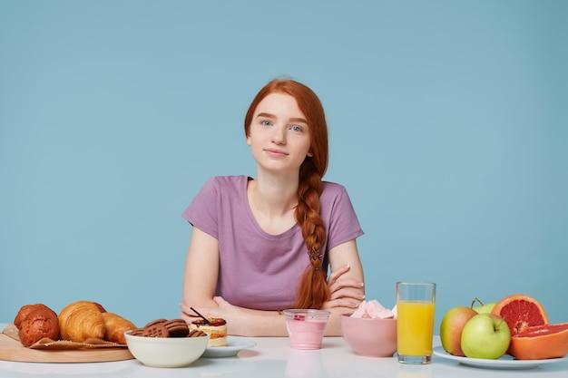 Piękna rudowłosa dziewczyna z zaplecionymi włosami siedząca przy stole, jadąca śniadanie
